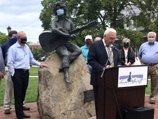 Sevier County Mayor Larry Waters and city officials gather around a masked Dolly Parton statue at the Sevier County Courthouse on Tuesday (photo courtesy of Leslie Ackerson/WBIR)