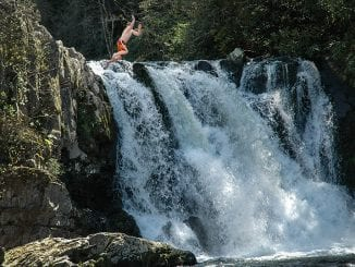 Abrams Falls makes for a beautiful photo-op, but it's a dangerous place to try and enter the water (don't do what this guy is doing) (stock photo/TheSmokies.com)