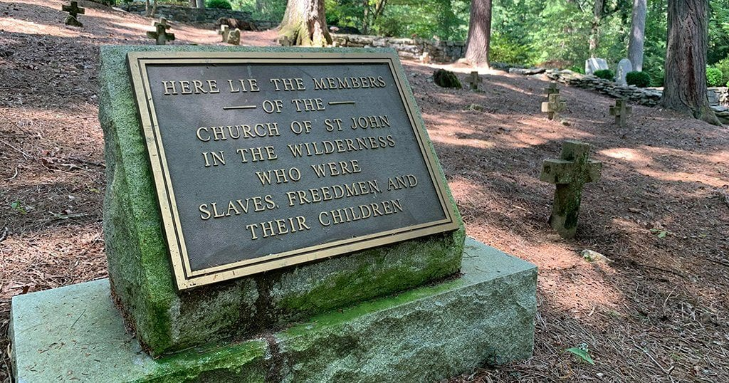 "A marker reads: ""Here lie the members of the church of St. John in the Wilderness who were slaves, freemen and their children)"" photo by John Gullion/TheSmokies.com"
